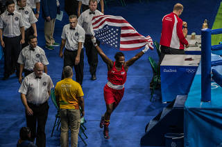 U.S. boxer Claressa Shields celebrates with an American flag after defeating Nouchka Fontijn of the Netherlands to win the gold medal in the women's middle weight class, in Rio de Janeiro, Aug. 21, 2016. (Mauricio Lima/The New York Times)