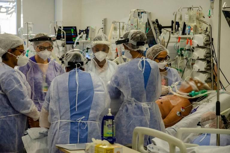 Profissionais da saúde equipados envolta de uma cama com paciente intubado
