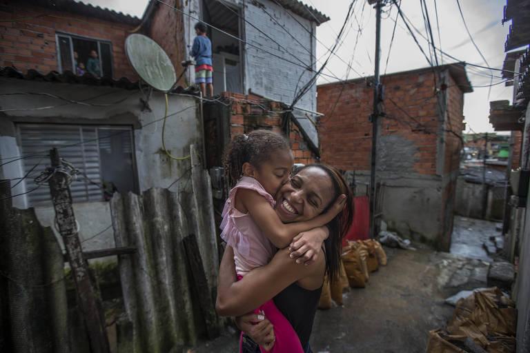 Tendo ao fundo uma casa de tijolos aparentes, com fios sobre uma rua estreita, mãe e filha se abraçam, e a menina, Heloísa, beija a mãe, Vailma