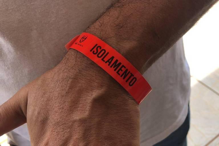 """homem com camiseta branca exibe pulseira vermelha com a palavra """"isolamento"""", por ter sido infectado pela Covid-19"""