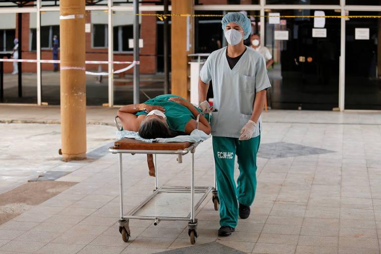 Profissional de saúde transporta paciente com coronavírus em hospital em San Lorenzo, no Paraguai