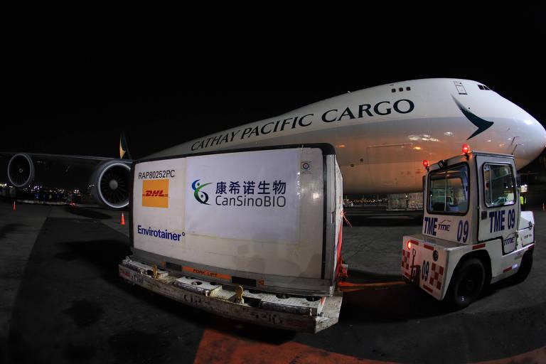 Avião branco com a inscrição Cathway Pacific Cargo ao fundo, com conteiner com inscrição em chinês e Cansino BIO em foto noturna feita em aeroporto