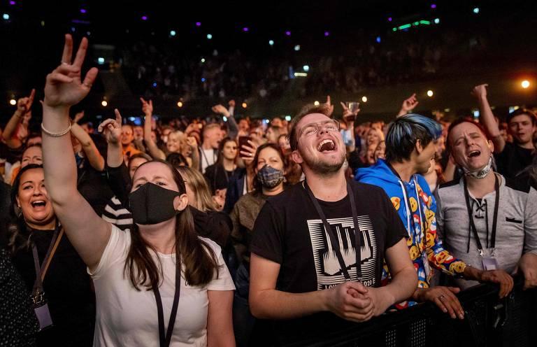 Com e sem máscara, jovens cantam e levantam os braços