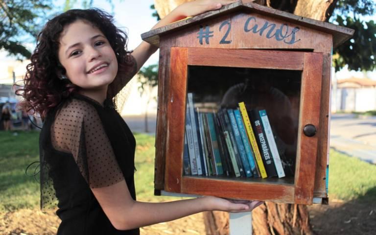 menina sorri olhando para a foto e segurando uma casa repleta de livros