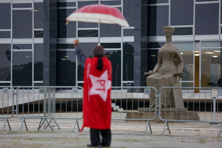 Petista comemora decisão favorável a Lula em frente ao Supremo Tribunal Federal, em Brasília