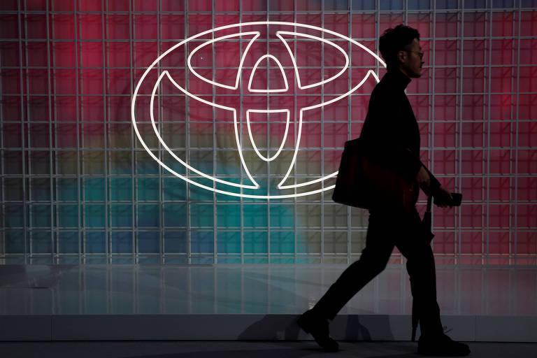 Um homem passa na frente do logo da Toyota, no Japão; Plano de continuidade de negócios da Toyota exige que fornecedores estoquem de dois a seis meses em chips para a montadora japonesa