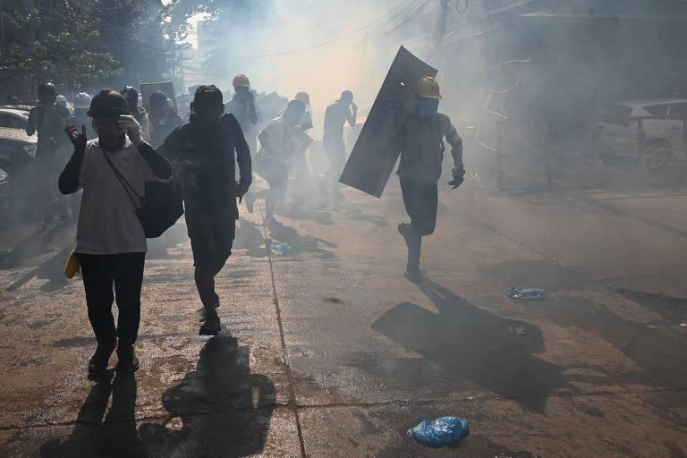 Manifestantes correm enquanto polícia dispara gás lacrimogêneo para conter protesto em Rangoon, em Mianmar