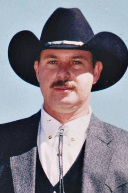 Homem de chapéu preto, terno, e camisa estilo cowboy