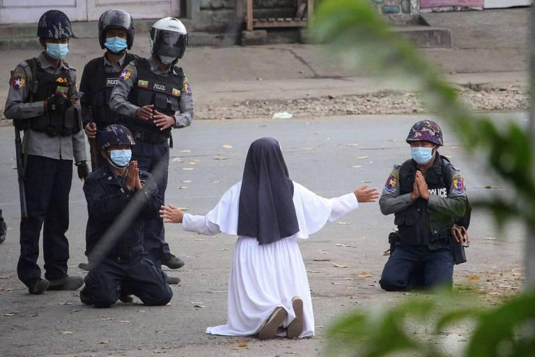 freira ajoelhada no asfalto com os braços abertos na frente da polícia