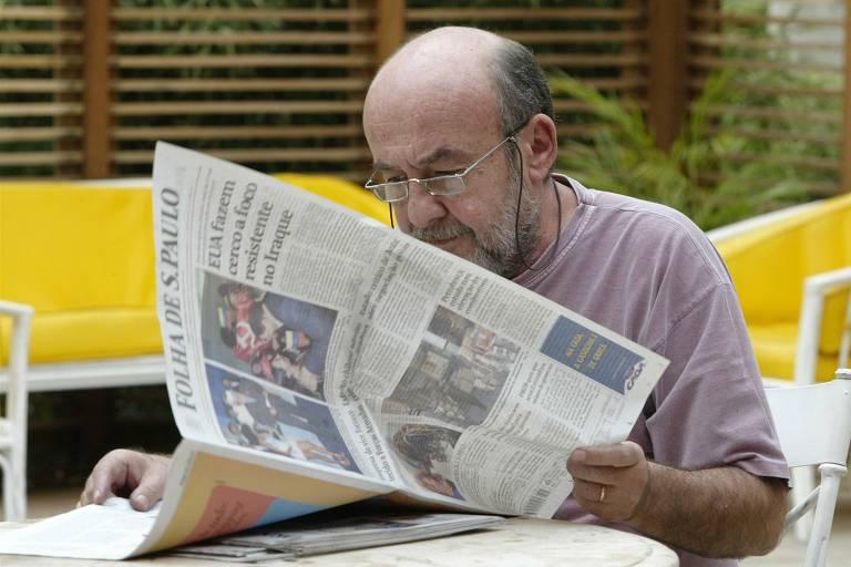 Ricardo Kotscho lê a Folha de S.Paulo. Ele aparece sentado a uma mesa virando a primeira página do jornal. Ele veste camiseta, tem pele clara, pouco cabelo, barba grisalha e usa óculos, preso a seu pescoço por um cordão. Ao fundo, vê-se cadeiras brancas com almofadas amarelas, brancas e um gradeado.