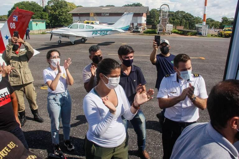 Pessoas de máscara aplaudem, olhando provavelmente para o piloto (ele não aparece na foto)
