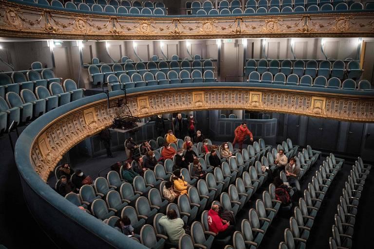 Poucas pessoas sentadas em cadeiras de teatro
