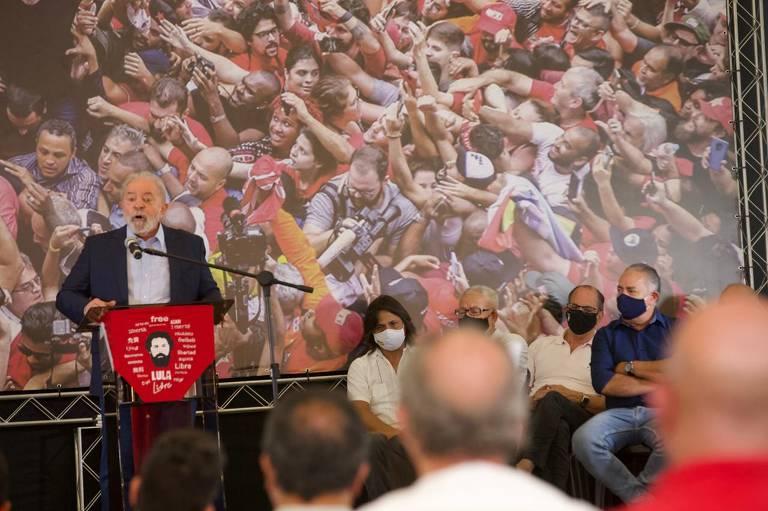 Lula discursa sobre palco. Ao fundo, foto em que uma multidão cerca ele ao sair do Sindicato dos Metalúrgicos de São Bernardo. Lula é um homem branco, de cabelos e barba grisalhos. Ele veste um terno.