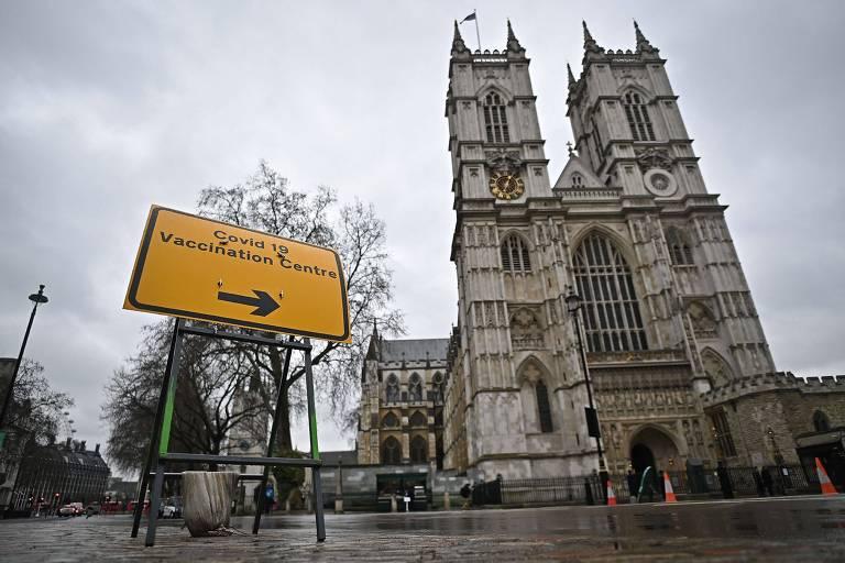 Placa amarela indica posto de vacinação apontando para igreja com duas torres , uma de cada lado da fachada