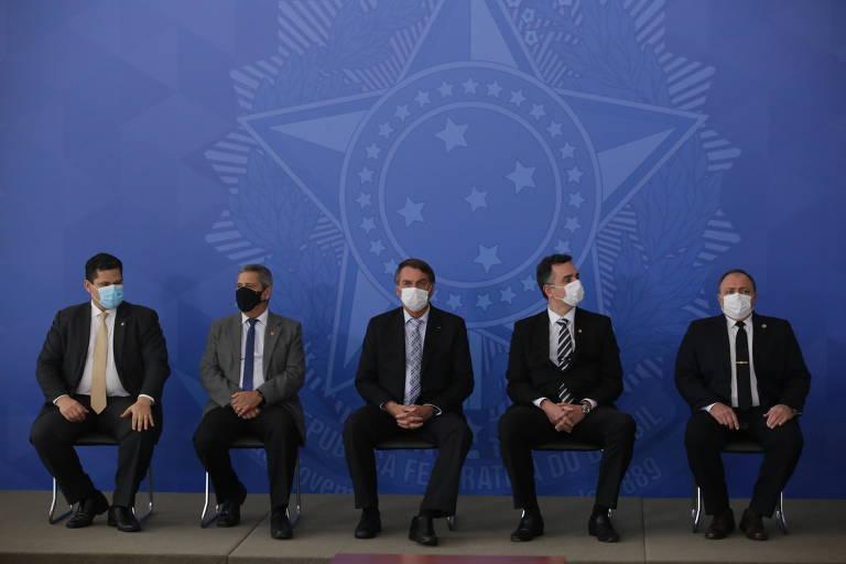 Cinco homens de terno, usando máscaras faciais, estão sentados em cadeiras montadas sobre um palco de fundo azul