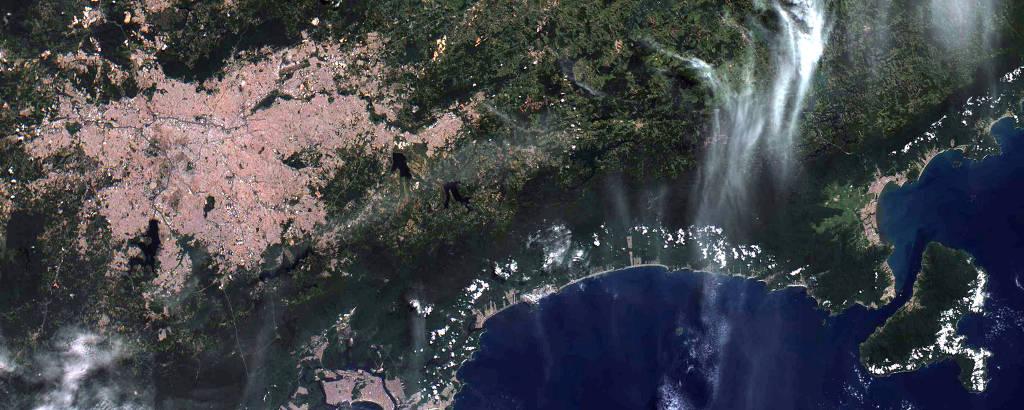Imagem de satélite mostrando uma área verde, de mata, próxima a uma aglomerado urbano; no canto inferior direito também é possível ver o mar