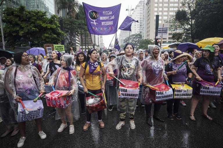 Fila de mulheres com instrumentos e cartazes protestam com capas de chuva em avenida