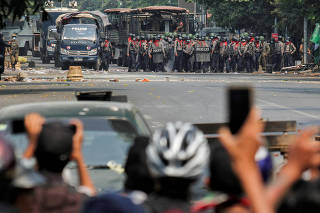 FILE PHOTO: Police stand on a road during an anti-coup protest in Mandalay
