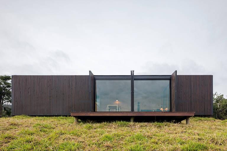 Casa em formato retangular, com janela grande no centro, em colina