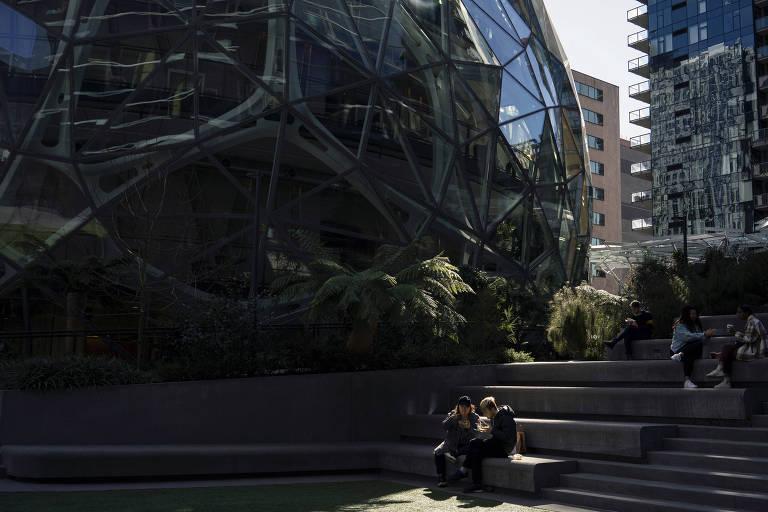 Pessoas almoçam fora da sede da Amazon, em Seattle, um ano após a OMS decretar o surto de coronavírus uma pandemia