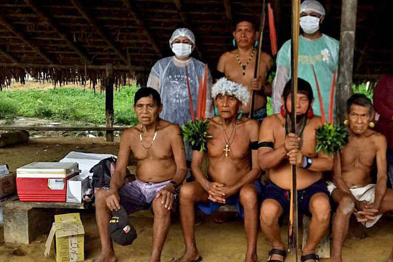 Indígenas e enfermeiros posam para foto dentro ao lado de cooler vermelho (onde provavelmente estavam as doses de vacinas),