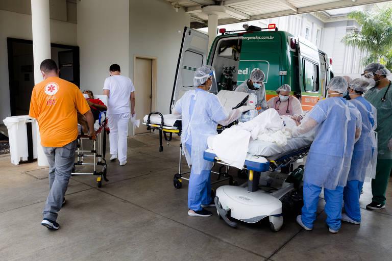 Equipe de profissionais da saúde auxiliam transporte de paciente em maca para hospital