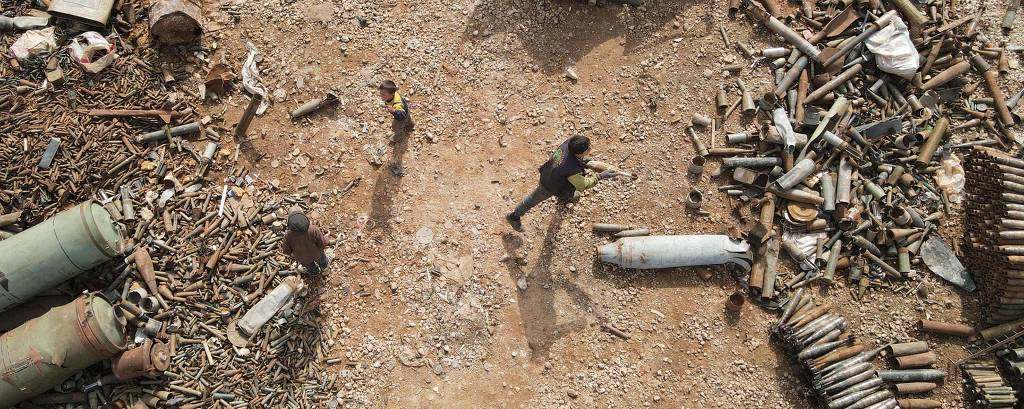 Crianças sírias separam sucata, que inclui cartuchos e invólucros de munições usadas, na província síria de Idlib