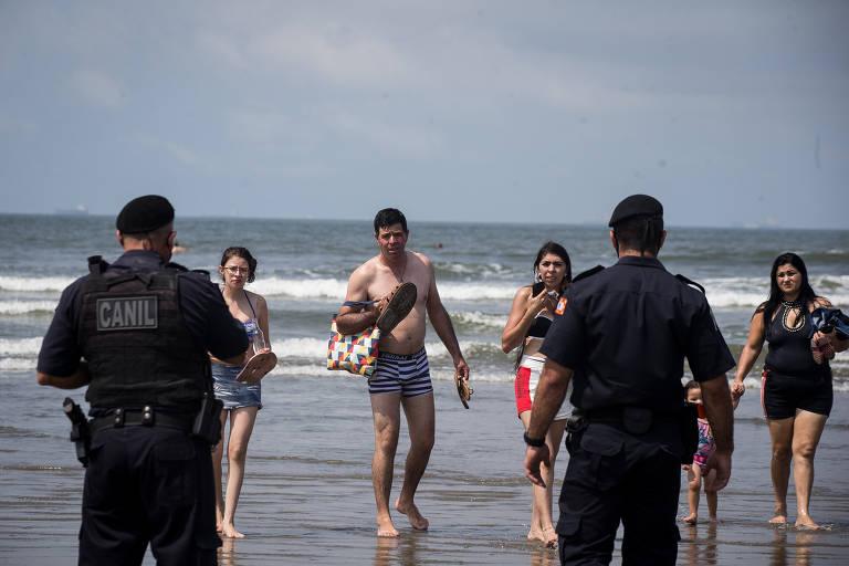 Policiais conversam com banhista durante operação para retirada de pessoas nas praias Jose Menino e Itararé, na divisa entre Santos e São Vicente
