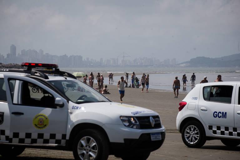 Carros da GCM de Santos são vistos na areia durante a operação de retiradas de banhistas