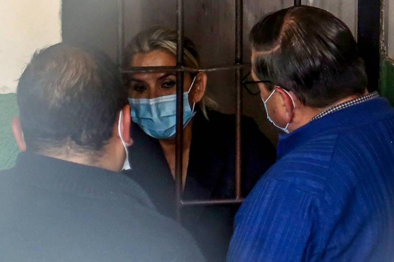 mulher loira usa máscara azul e conversa com dois homens por de trás das grades