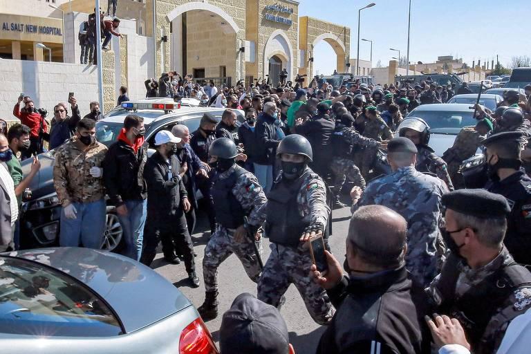 Forças policiais da Jordânia tentam conter manifestantes que protestam na frente do novo hospital al-Hussain na cidade de  Salt, após pacientes de covid-19 morrerem por falta de fornecimento de oxigênio.
