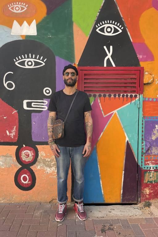 homem diante de parede colorida cheia de símbolos