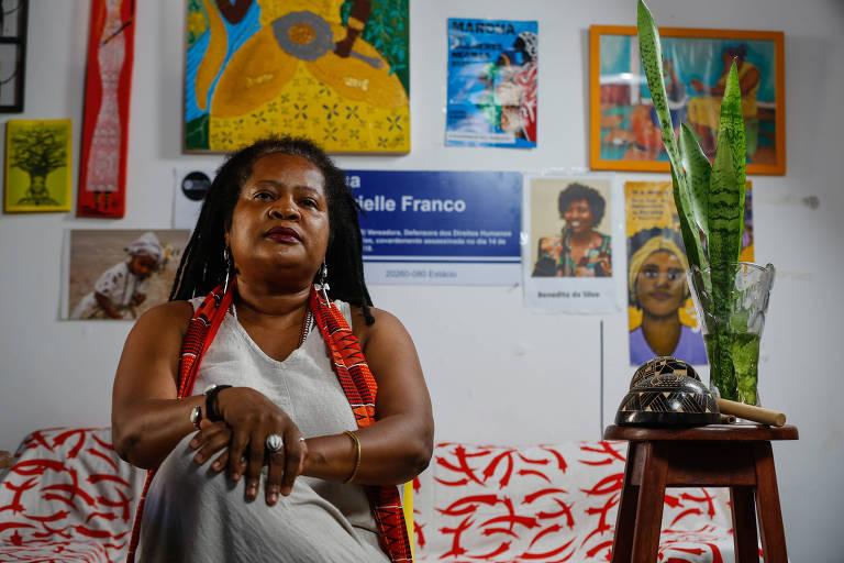 """A socióloga Vilma Reis, 51, em sua casa em Salvador, decorada com uma placa de rua com o nome de Marielle Franco, um retrato da deputada federal Benedita da Silva (PT-RJ) e um quadro com representação de Oxum, """"divindidade africana e afrobrasileira que trata do poder das mulheres, da transformação e da vida"""""""