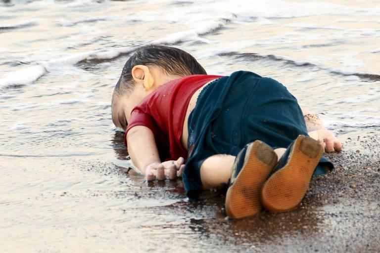 cadáver de criança pequena estendido na beira do mar