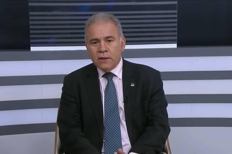 Marcelo Queiroga, veste camisa social branca, paletó escuro e gravata azul. Ele está ao centro da foto, sozinho, sentado