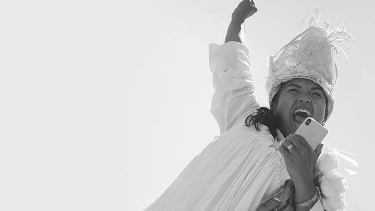 Mulher negra com vestes branca segura celular e levanta seu outro braço em tom de comemoração