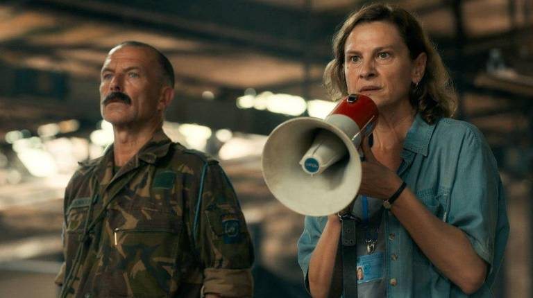 Homem vestido de militar ao lado de mulher que segura altofalante