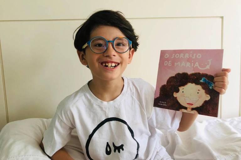 Menino sorridente e de óculos segura na mão esquerda um livro com capa cor de rosa