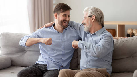 Excited millennial man sit on couch spend time with elderly father talking enjoying leisure time at home, smiling grown son relax on sofa with senior dad give fists bump, spend family weekend together
