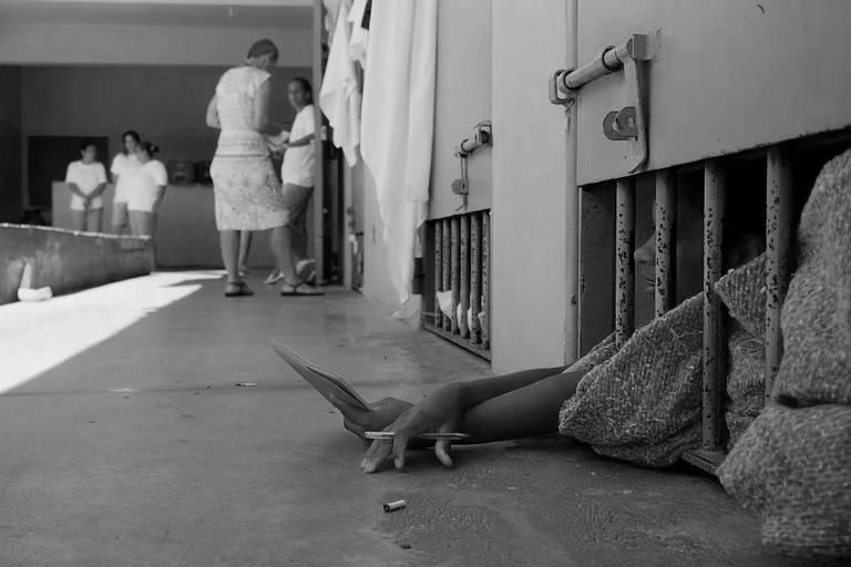 Mulher escreve em caderno na cela de penitenciária feminina