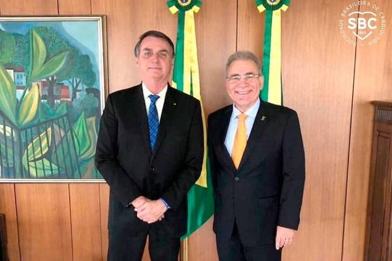 Bolsonaro e Queiroga estão de pé, posando para a foto. Os dois vestem terno escuro e gravata (azul a de Bolsonaro e laranja a de Queiroga)