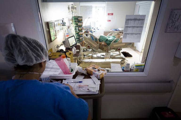 Imagem mostra enfermeira no canto esquerdo e um paciente em leito de UTI, separado da profissional de saúde por um vidro