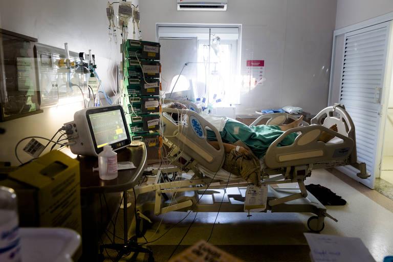 Imagem mostra homem deitado em cama hospitalar, cercado por equipamentos