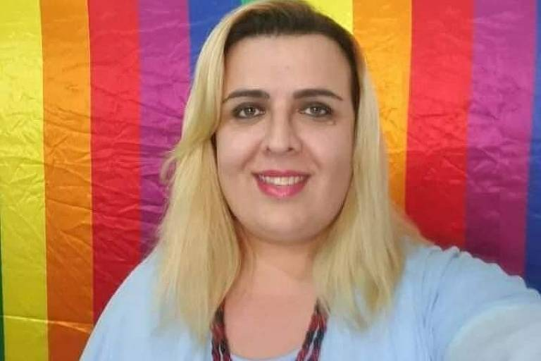Valéria Rodrigues posa em frente à bandeira do movimento LGBTQI+