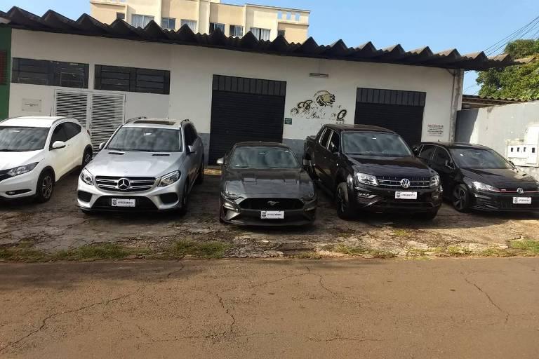 Imagem mostra cinco carros com a inscrição 'apreendido' no local das placas