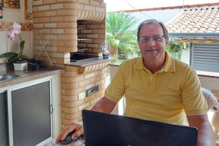 Homem de camisa polo amarela na frente do computador sorrindo