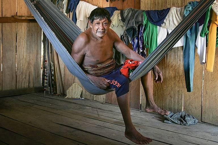 Aruká Juma posa para a foto sentado em uma rede instalada em um ambiente de madeira. Ele está sem camisa, de bermuda azul escura e descalço
