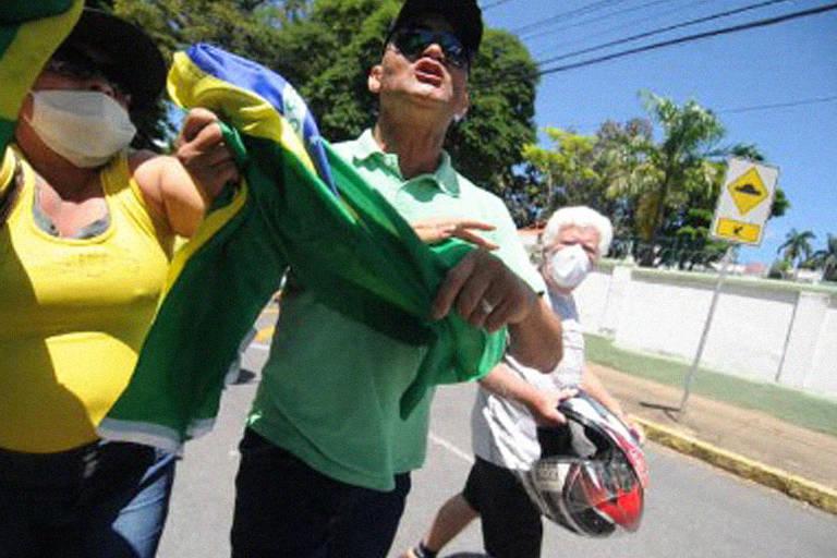 Homem com bandeira do Brasil gritando