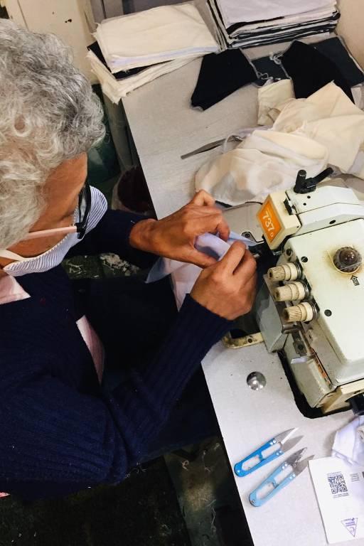 mulher idosa de cabelos brancos costura absorvente em máquina