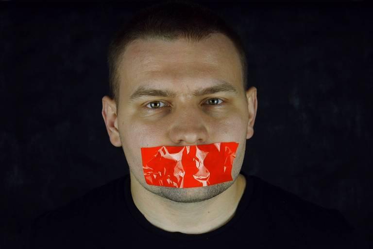 Homem com boca fechada por mordaça